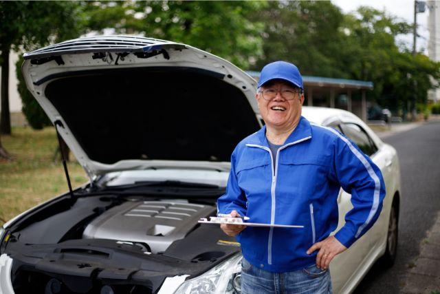車のボンネットを開けて検査をする整備士